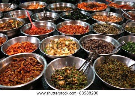 Metal bowls full of various fermented vegetables. Photo taken on a traditional food market in  South Korea - stock photo