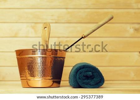 Metal bucket and towel in sauna. - stock photo