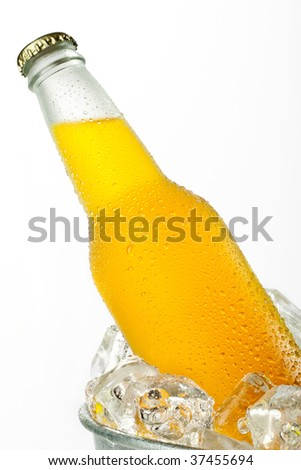 Metal bucket full with ice and a glass bottle of orange beverage - stock photo