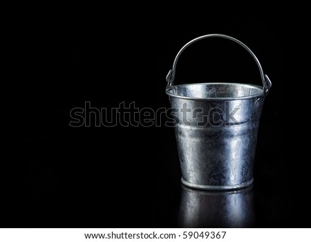 Metal bucket on black with copy space - stock photo