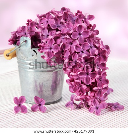 metal bucket with a bouquet of purple lilac spring flowers on textured background - stock photo