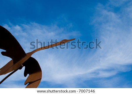 Metal Canada goose against blue cloudy sky.