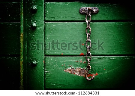 Metal chain hanging on old wooden train carriage door - stock photo
