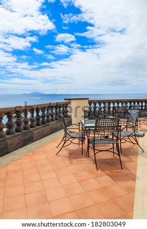 Metal chairs with glass table on terrace of lighthouse building on coast of Madeira island, Portugal  - stock photo
