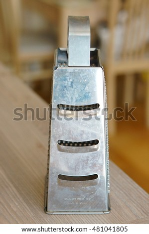 Metal cheese grater with dirt spots on wooden table