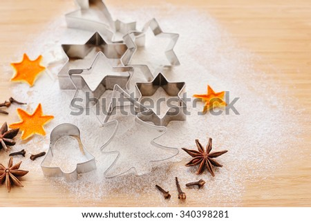 Metal Christmas Cookie Cutters in Freshly Sifted Flour on Wooden Chopping Board