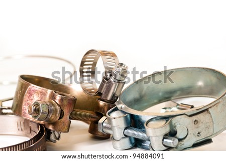 metal clips for connecting different types of pipes on a white background - stock photo