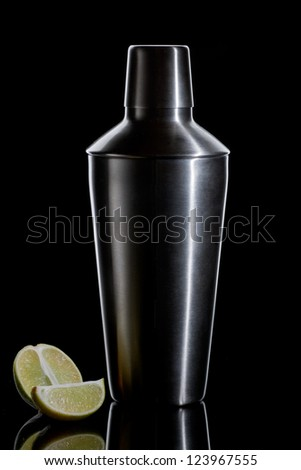 Metal cocktail shaker with pair pieces of lime on a black background