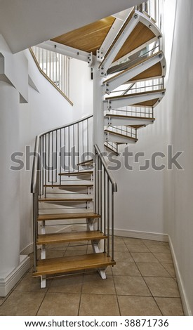 metal construction and wooden steps spiral staircase - stock photo