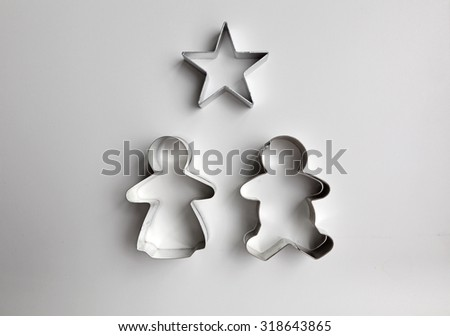 Metal cookie cutter of gingerbread man, woman and a star on a white kitchen top. - stock photo