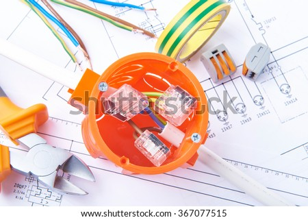 Metal cut pliers, isolation tape and connected cable in electrical junction box, lying on electrical diagrams. Work tools for engineer jobs, concept of electrical works.