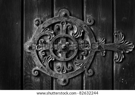metal decoration on the old and rusty wooden door black and white - stock photo
