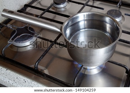 Metal dipper on the gas stove in the kitchen - stock photo