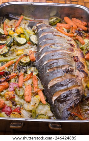 metal dish with baked fish and vegetables