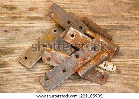 metal door hinge on a grungy wooden background - stock photo