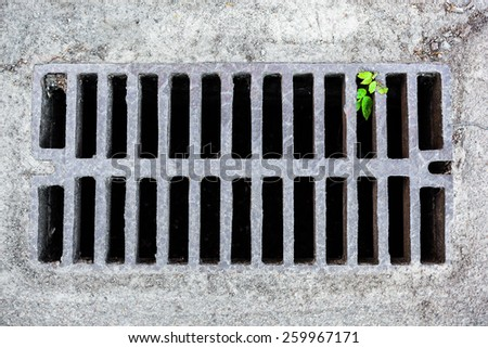 Metal drain grate in the sandy surface - stock photo