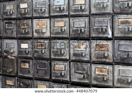 Metal drawers. Closed archive storage, filing cabinet interior. aged silver metallic boxes with index cards. library service information security management. - stock photo