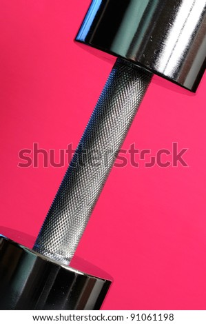 Metal Dumbbell on Pink Background - stock photo