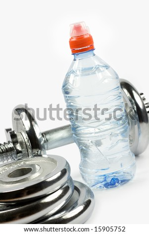 Metal dumbbell with bottle of water and weights - stock photo