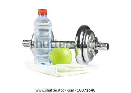 Metal dumbbell with green apple, bottle of water and towel