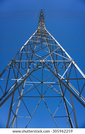 Metal electric power line tower stands under a bold blue sky. - stock photo