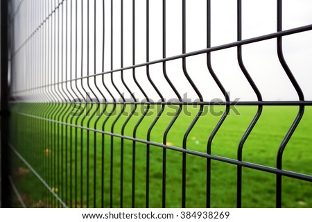 Metal fence wire, grass and sky in the background - stock photo