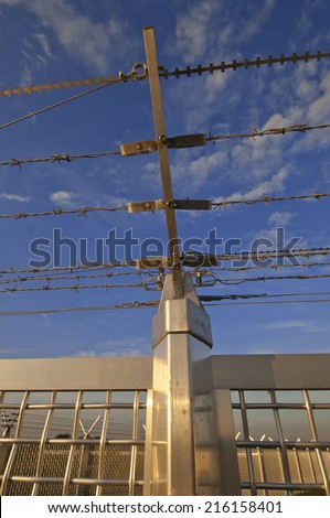 Metal fence with barbed wire - stock photo