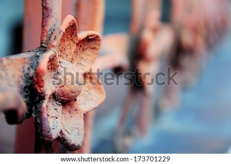 Metal fence with floral ornament - depth of field focusing on the floral ornament diminishing to very soft focus - stock photo