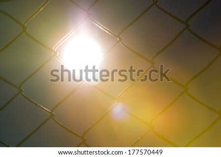 Metal fence with shining sun - stock photo