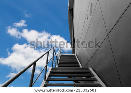 Metal fire escape or emergency exit on Black Wall of Building With Blue Sky and White Cloud