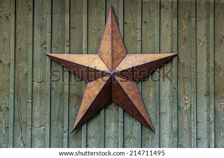 metal five pointed star on a rough wood wall - stock photo