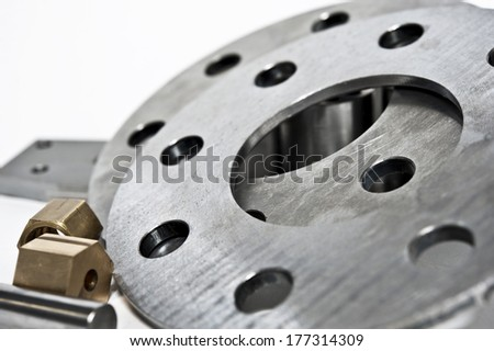 Metal flanges and brass nuts. CNC milling/lathe industry. Closeup. - stock photo