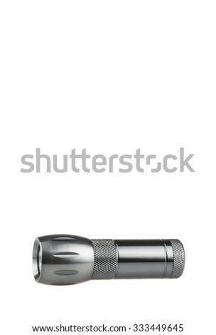 Metal flashlight over white background - stock photo