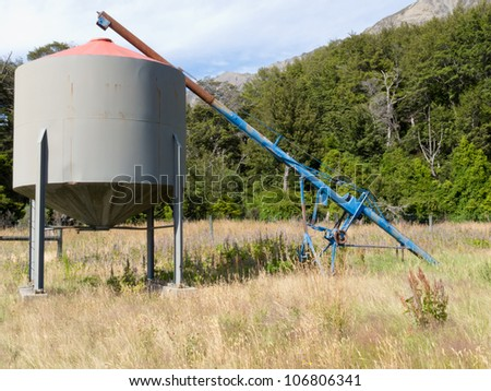 Metal fodder fermenting silo storage tank raised on supports with an inlet conveyor pipe for filling it through a hole in the top standing in grassy agricultural field