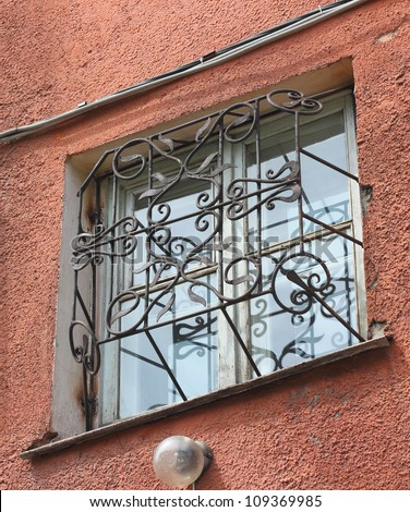 metal forged carved lattice at a plastic white window - stock photo