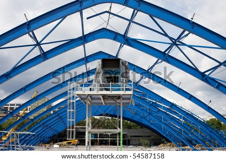 Metal frame structure on construction site of the shopping mall building - stock photo