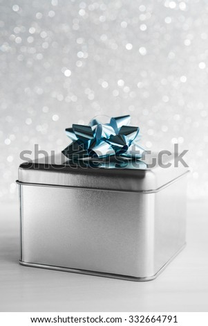 Metal gift box on white glitter background. Merry christmas card. Winter holidays. Xmas theme. Happy New Year. - stock photo