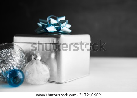 Metal gift box with blue bow and xmas baubles on white and black wooden backgrounds. Merry christmas card. Winter holidays. Xmas theme. - stock photo