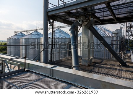 Metal grain elevator inagricultural zone - stock photo