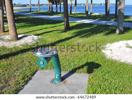Metal green public water fountain next to a beach walkway in St. Petersburg, Florida - stock photo