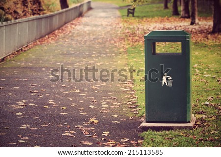 Metal green rubbish container by the walk way in the city autumn park - stock photo
