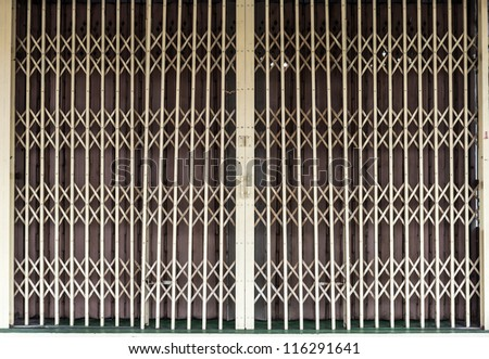 Metal grille sliding door against a metal folding door for textural background. - stock photo