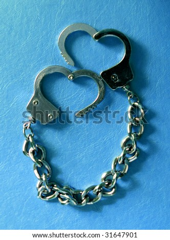 metal handcuffs in shape of heart at blue background - stock photo