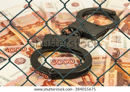 Metal handcuffs on the background of Russian rubles under wire netting (lattice) - stock photo