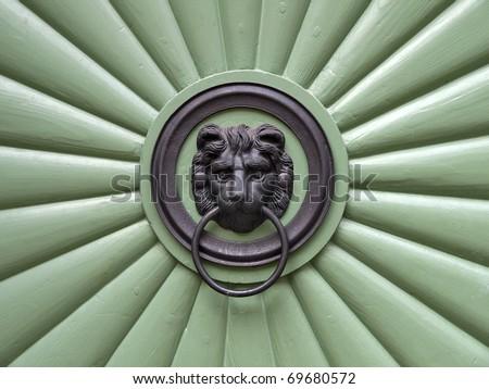 metal head of lion on the front door - stock photo