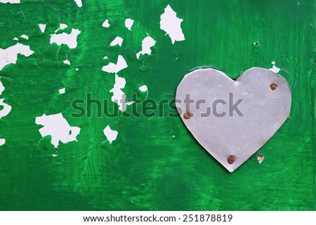 metal heart shape on green painted surface - stock photo