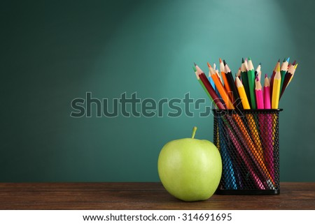metal holder with crayons and green apple on desk on green chalkboard background - stock photo
