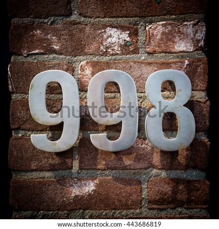 metal house number nine hundred and ninety eight. - stock photo