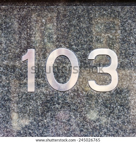 metal house number one hundred and three. - stock photo