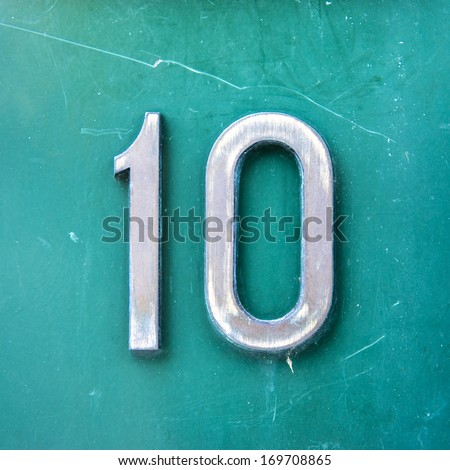 metal house number ten on a green background. - stock photo